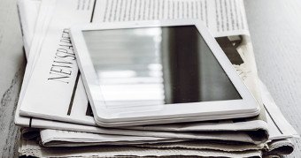 tablet laying on top of newspaper
